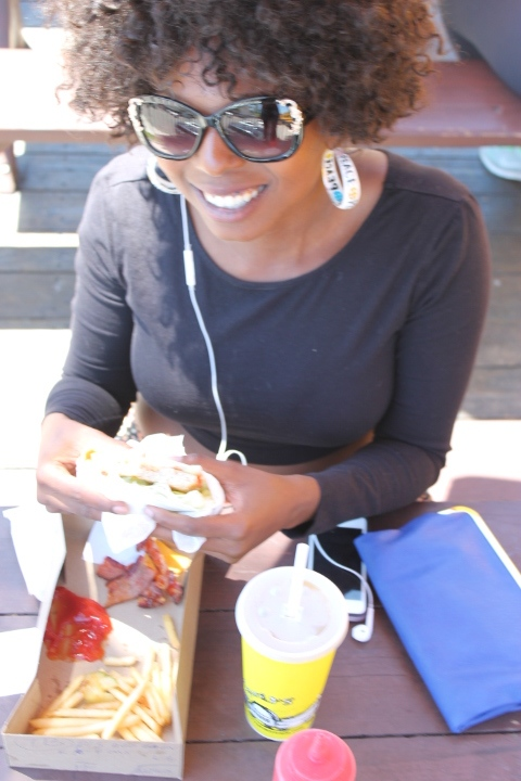 Cool black woman eating a hot dog